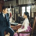 Lee Byun Hyun in Western clothing looks at Kim Tae-ri in a hanbok as she sits in an office