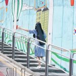 A girl walks up an outdoor stairway next to a colorful wall while carrying a violin in the Kdrama Still 17