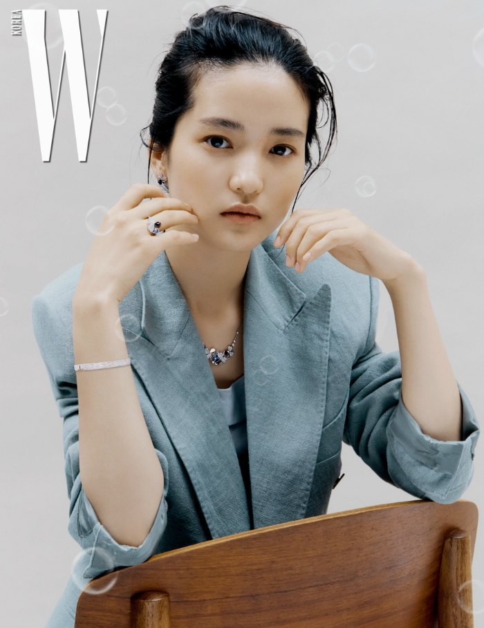 Kim Tae Ri sitting cavalierly on a chair showcasing a turquoise jacket and delicate jewelry